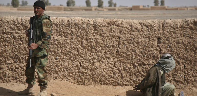 An Afghan National Army soldier stands guard as a blindfolded suspected Taliban sits with his hands tied on the ground in Marjah, Afghanistan, Thursday, Feb. 18, 2010 (AP Photo/Jerome Starkey)